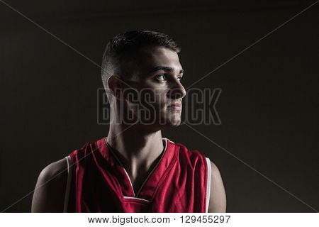 Basketball player looking away against a black background