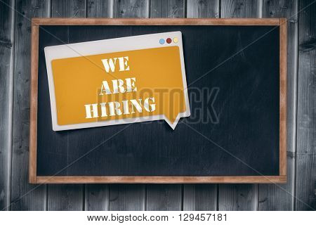 We are hiring message against blackboard with copy space on wooden board