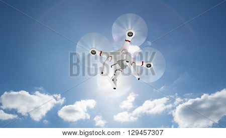 Image of a drone against cloudy sky with sunshine