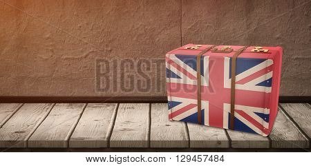 Great Britain flag suitcase against wooden table on a texture wall