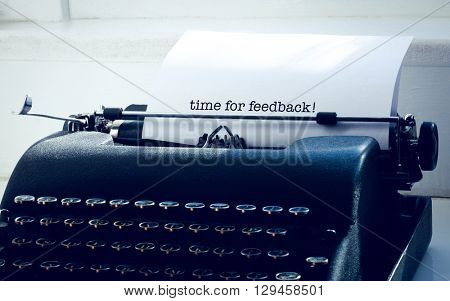 The word time for feedback! against typewriter on a table