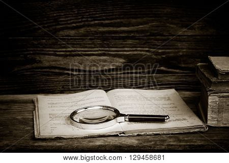black and white photo. open old book with a magnifying glass and a stack of books on a wooden table. the concept of the study the study. with space for text