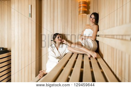 Two fit and beautiful women relaxing in a sauna