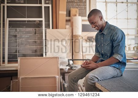 Handsome young designer of African descent, smiling while reading a message on his mobile phone, and sitting on a work bench in his workshop studio