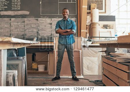 Full length portrait of a handsome young business owner of African descent, standing with his arms crossed and smiling confidently at the camera with his busy studio workshop around him