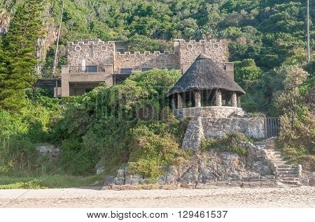 KNYSNA SOUTH AFRICA - MARCH 5 2016: A house on the slopes of a hill at the beach in Noetsie. Noetsie is a popular tourist attraction due to the houses that were built to look like castles.