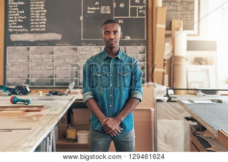 Proud business owner of African descent, standing in his woodwork studio and looking seriously at the camera with workbenches on either side