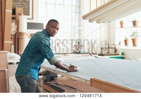 Handsome young designer of African descent working with pen and paper at a large work table in his workshop studio, and turning to look at the camera