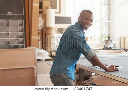 Young African man working in his design studio, turning to smile happily at the camera