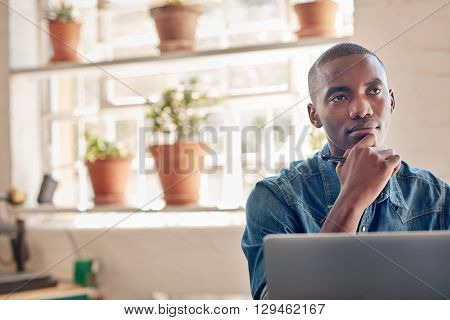 Handsome small business owner of African descent, sitting in his beautifully lit studio in front of his laptop, looking away into the distance with a very thoughtful expression