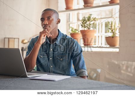 Handsome young designer of African descent sitting in his beautifully lit studio, looking thoughtfully into the distance with his laptop open in front of him