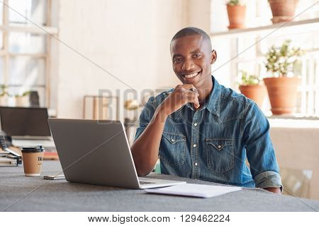 Portrait of a handsome African designer sitting at a work table in his studio with beautiful lighting, smiling comfortably at the camera with his laptop open in front of him