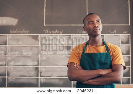 Handsome young craftsman of African descent standing with his arms folded and wearing an apron, thinking about his entrepreneurial future plans