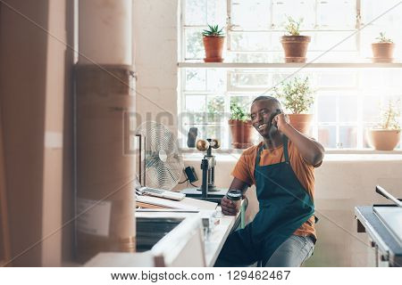 Handsome crafstman and small business owner of African descent, sitting at his desk in his workshop studio, laughing while talking on his mobile phone