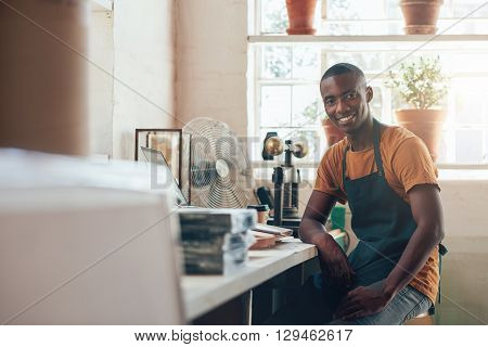 Portrait of a relaxed and confident young designer and craftsman of African descent, smiling at the camera while sitting in his studio and workshop, from where he runs his small business