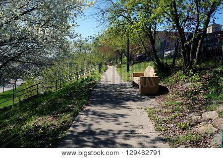 One may sit on a bench and enjoy the view of downtown Joliet, Illinois, and of the riverfront, from the top of the bluff above Billie Limacher Bicentennial Park.