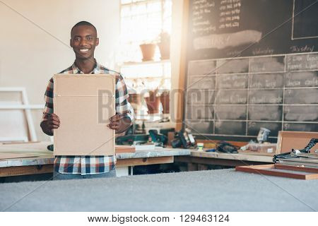 African owner of a small business that manufacture picture frames, smiling at the camera while holding a framed picture made in his workshop