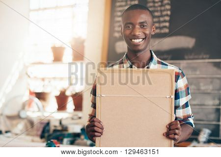 Young business owner of African descent smiling proudly at the camera while holding a picture frame which was made in his own picture framing workshop