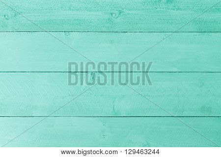 Pastel green stained wood background texture with horizontal parallel boards woodgrain and copy space full frame