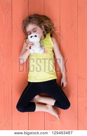 Cute supple young girl sleeping with her plush toy cat held to her face lying on her back with folded legs on a colorful orange wooden deck viewed from overhead