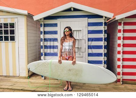 Portrait of beautiful young surfer woman with white top and bikini holding surfboard over a beach striped huts background. Summer leisure concept.