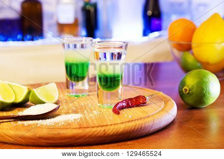 two alcoholic drinks shot on a wooden board with fruit