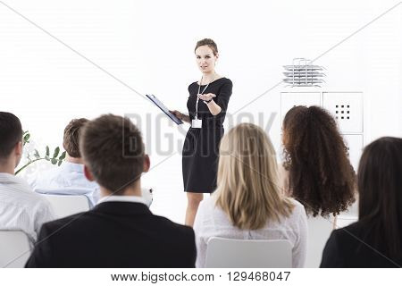 Shot of a young manager talking to the group of her coworkers