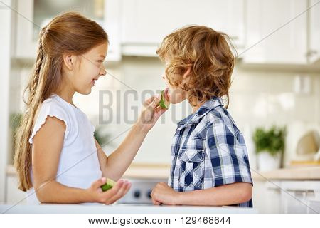 Girl daring boy to lick on a lime fruit in the kitchen