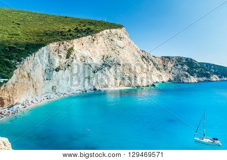 Porto Katsiki beach in Lefkada island, Greece. Beautiful view over the beach. The water is turquoise and there are tourists on the beach and a boat on the sea.