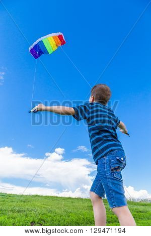 Boy playing with colorful kite on the green hill
