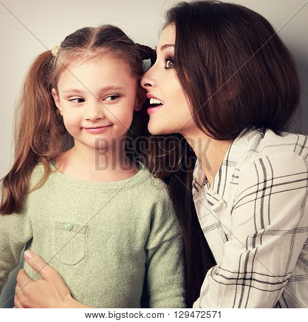 Joying Young Mother Whispering The Secret To Her Funny Grimacing Daughter In Ear In Studio. Toned Cl