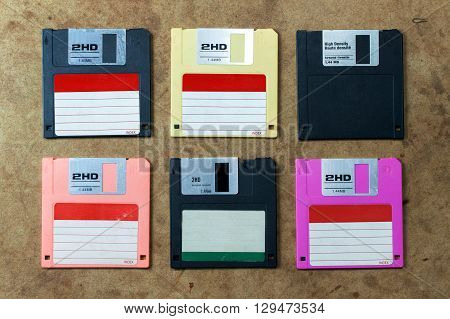 floppy disk in various colors. flat lay on wood board