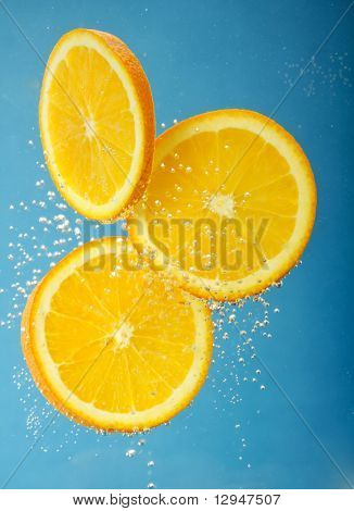 Fresh orange dropped into water