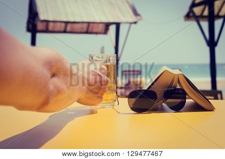 Man's hand holding a glass of beer in a beach cafe. Vacation theme concept