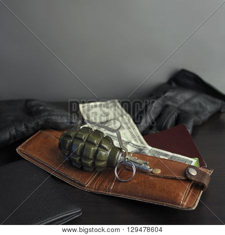 Hand grenade in focus laid on a wallet with passport next to a pair of leather gloves. Studio square shot