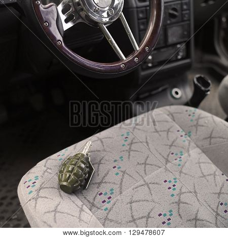 Hand grenade on a car front seat selective color shot concept of terrorism