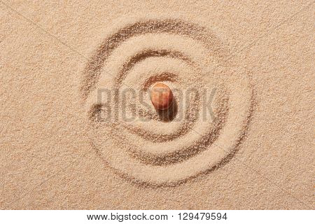 Spiral Drawn On Beach Sand With Pink Round Sea Stone In Centre
