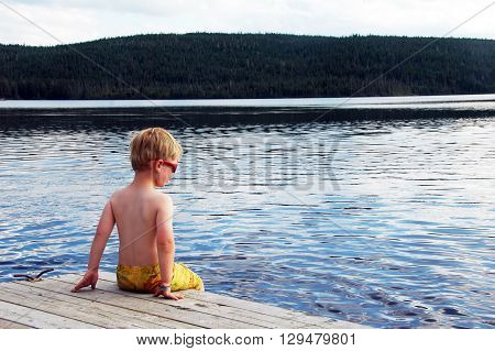 Picture of a boy sitting on a jetty at Lac St-Anne in National Park of Grands-Jardins, Quebec, Canada.