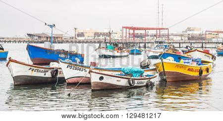 Paracas - Peru October 15 2014: View of a group of anchored fisher boats in a cloudy morning in Paracas Peru