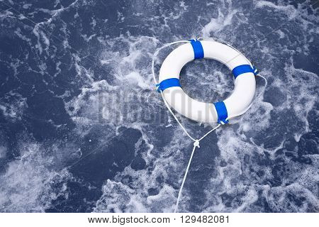 White lifebuoy lifebelt life saver rescue in a ocean storm full of foam
