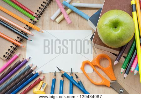 School supplies and white paper background ready for your design. (Back to school concept)