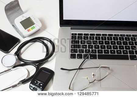 close up of doctor's desk with Laptop Stethiscope and other devices