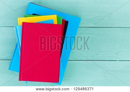 Top down view of red yellow and blue blank hardcover books on smooth wooden table with copy space