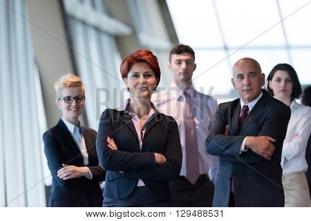 Diverse business people group standing together as team  in modern bright office interior. Redhair senior woman in front as leader