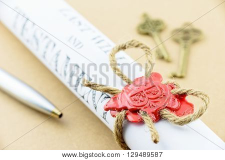 Rolled up scroll of Last will and testament that fastened with natural brown jute twine hemp rope sealed with sealing wax and stamped with alphabet letter B. Decorated with two antique brass keys.