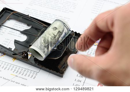 Man's right hand is preparing to pick a rolled up scroll of US 100 dollar bill with portrait / image of Benjamin Franklin on a black rat trap. Using money as a bait to lure someone for illegal things.