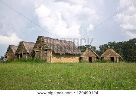 Neolithic mud dirt house village with thatched roof on green spring meadow