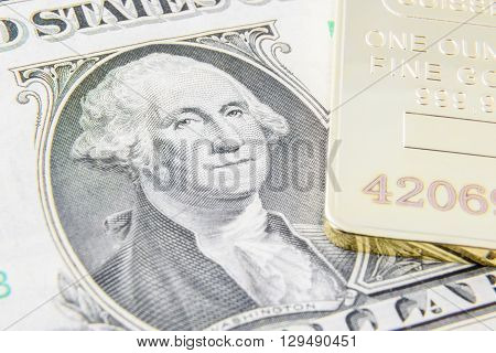 US one dollar bill with image / portrait of George Washington and gold bullion. A concept of the two most popular currency reserve in all countries in the world.
