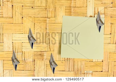Blank piece of paper attached on an old house bamboo wooden wall with Japanese ninja weapons. Copy space for leaving several messages i.e. notes reminder order information suggestion memo etc