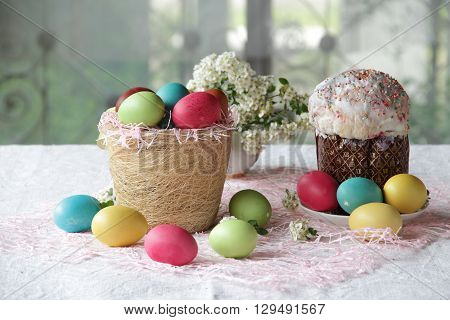 Easter cake and painted eggs in the basket on the table